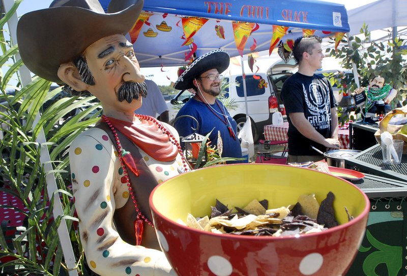 """Paul and Cameron Williams of Scarborough serve chili to visitors during the Southern Maine Regional Chili Cook-off Sunday. Offering chips in the foreground is a character the Williamses referred to as """"Slim Density."""""""
