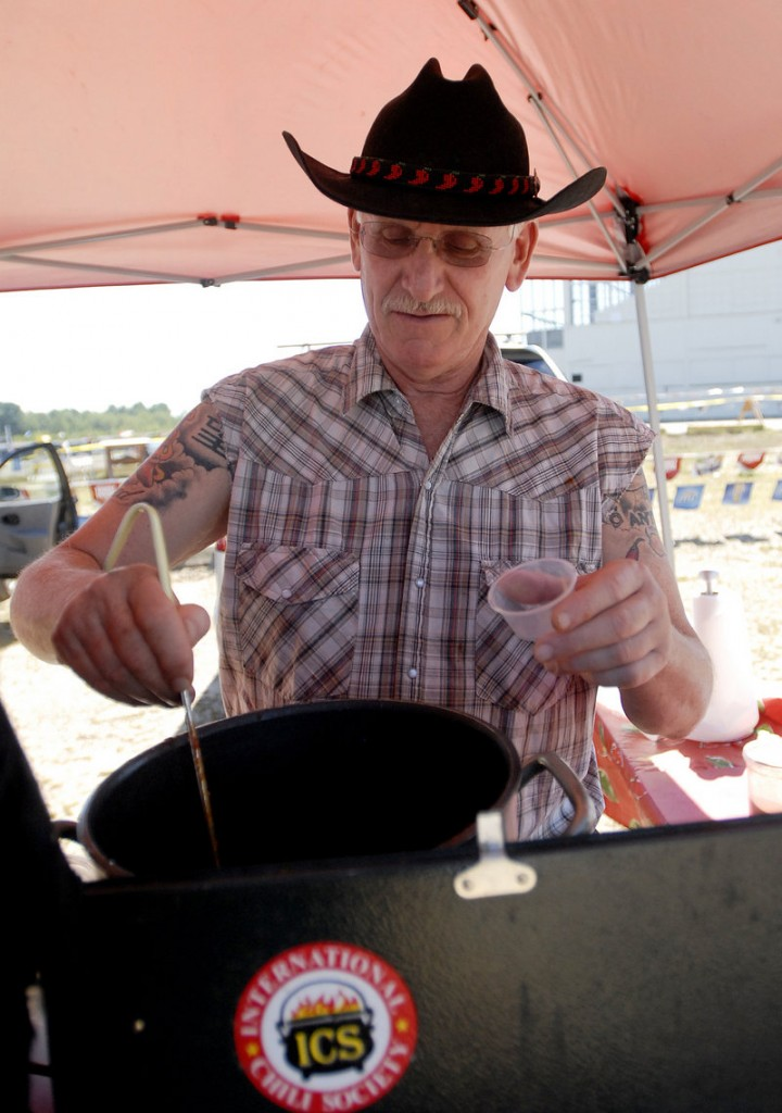 Dave Schulman of Avon, Conn., serves chili during the cook-off at Scarborough Downs. Competitors included 18 members of the International Chili Society and 17 others.