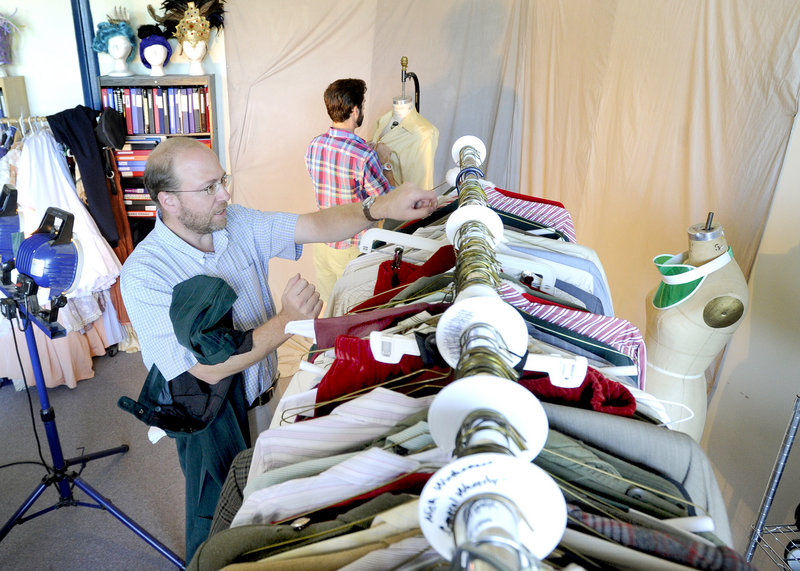 Reporter Ray Routhier looks through racks of costumes with Jacob Freund, who runs a costume rental business for the Maine State Music Theatre in Brunswick. The costumes are grouped by show and are rented to theaters nationwide.