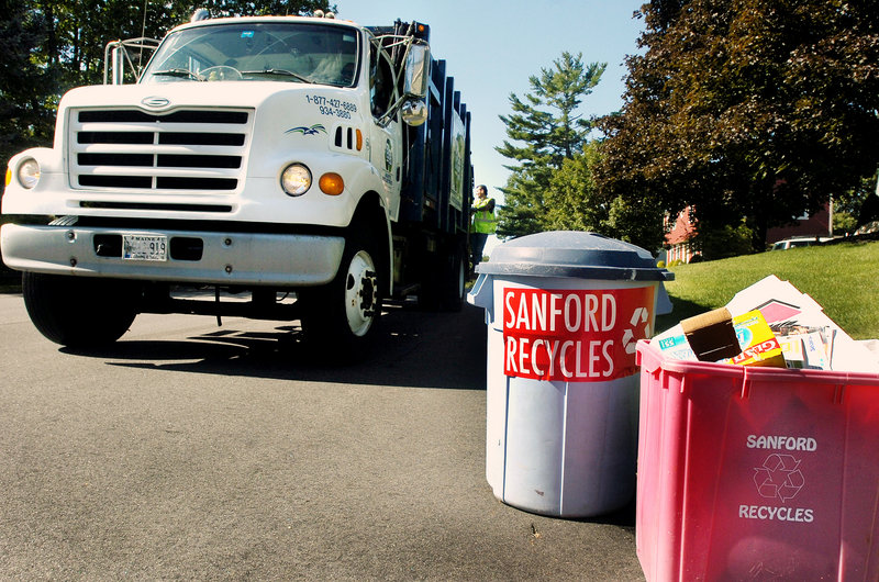 Sanford Public Works Department workers pick up items to recycle. Recycling has increased since the town instituted a pay-per-bag system for trash disposal.