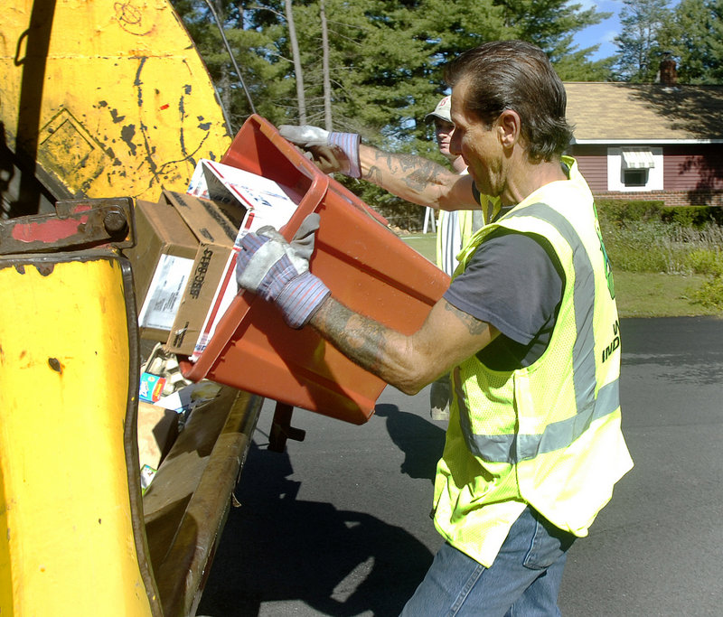 Sanford sanitation worker Steve Shaw dumps recyclable items.