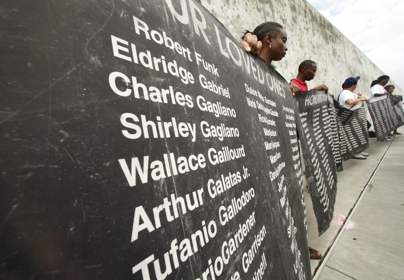 People hold up a banner bearing the names of those who died in Hurricane Katrina, in front of the Industrial Canal floodwall during a public commemoration of the fifth anniversary of the hurricane in New Orleans' Lower 9th Ward on Sunday.