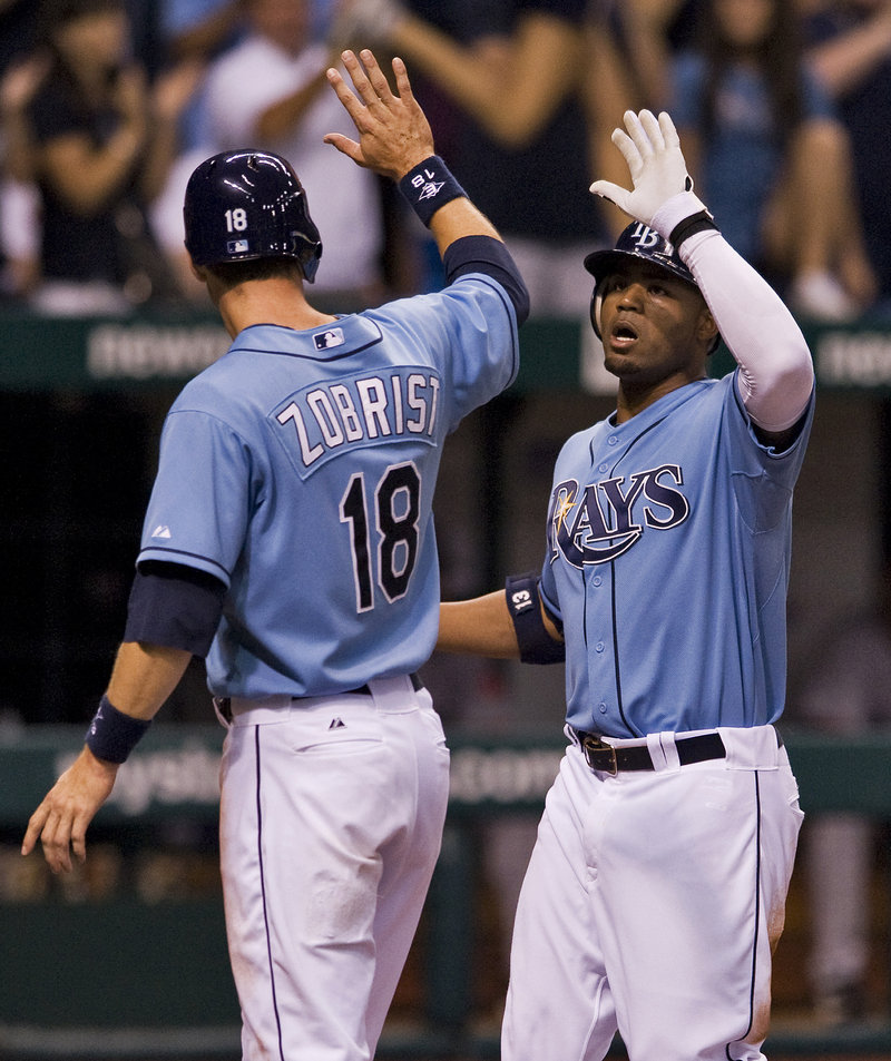 Ben Zobrist, left, congratulates Rays teammate Carl Crawford after scoring on Crawford's two-run homer in the sixth inning.