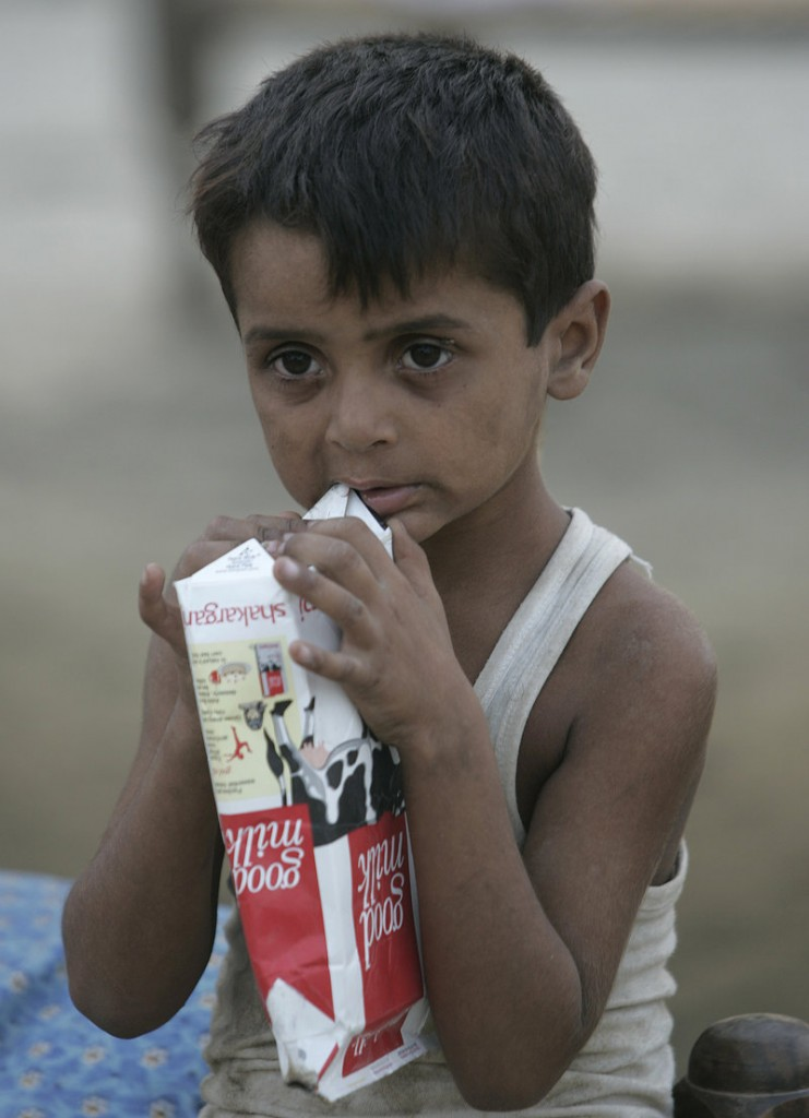 A boy chews on an empty milk carton Monday at a camp for people displaced by floods at Hazrat Mosa Wala in Punjab province, Pakistan. The floods are one of the biggest disasters in recent world history.
