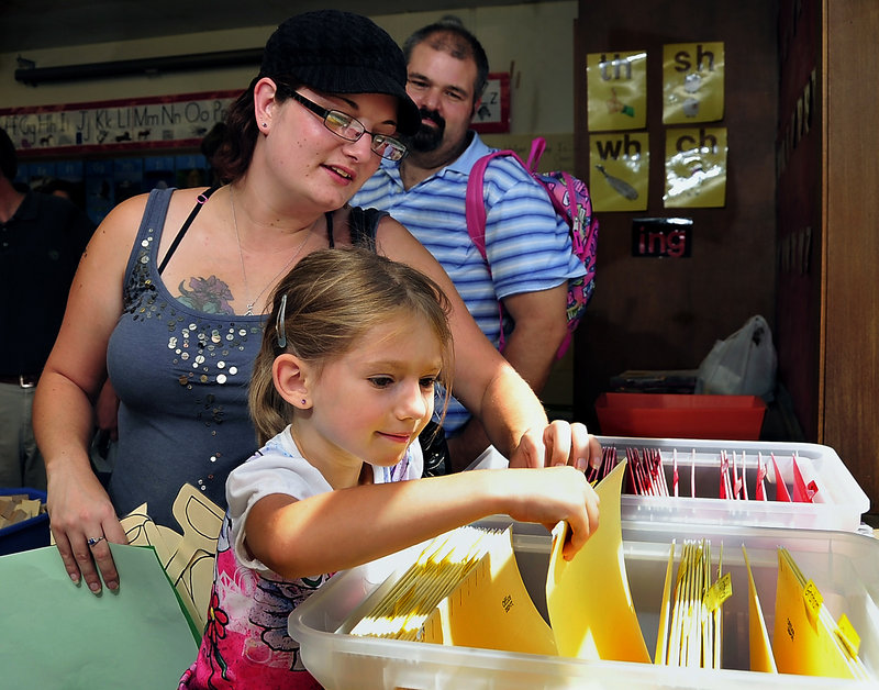 Emma Campbell, 5, is happy to find the folder with her name on it as she begins kindergarten Monday at the Narragansett School in Gorham. Helping out is her mother, Dawn Campbell, with fiance Jeff Meserve.