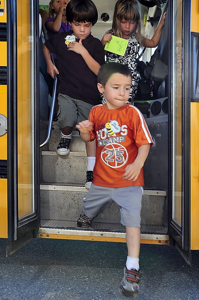 Joseph Cowan, 5, steps off the bus with fellow kindergartners Monday at the Narragansett School. Behind him are Shane Johnson, left, and Faith Connelly.