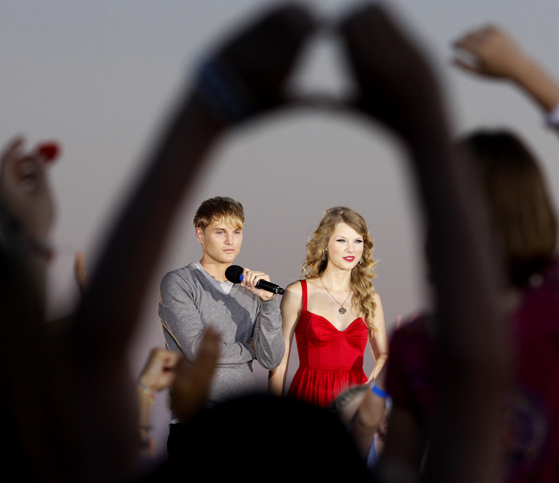 """A fan makes a heart symbol as country music star Taylor Swift and British actor Toby Hemingway talk about Swift's new music video, """"Mine,"""" in which Hemingway co-stars, at St. Ann's Church in Kennebunkport on Friday."""