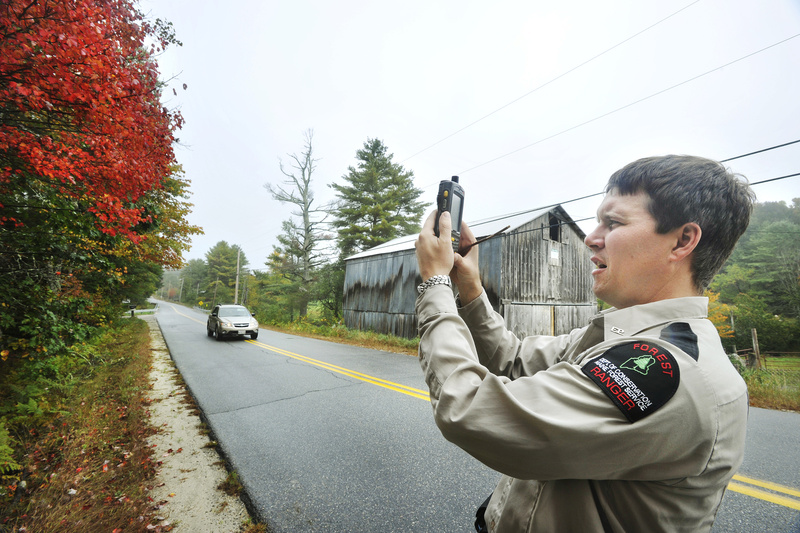 Art Lavoie, a forest ranger with the Maine Forest Service, files a foliage report each week that appears on the state's foliage website, www.mainefoliage.com. Here, Lavoie uses his PDA to photograph examples of the foliage on Mayall Road in Gray.
