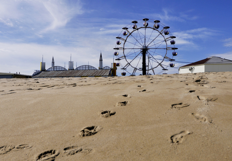 Footsteps in the sand lead away from Palace Playland in Old Orchard Beach on Tuesday. The crowds are mostly gone on the beach and the rides are closed until next season, but the amusement park's large arcade will be open weekends through Columbus Day.