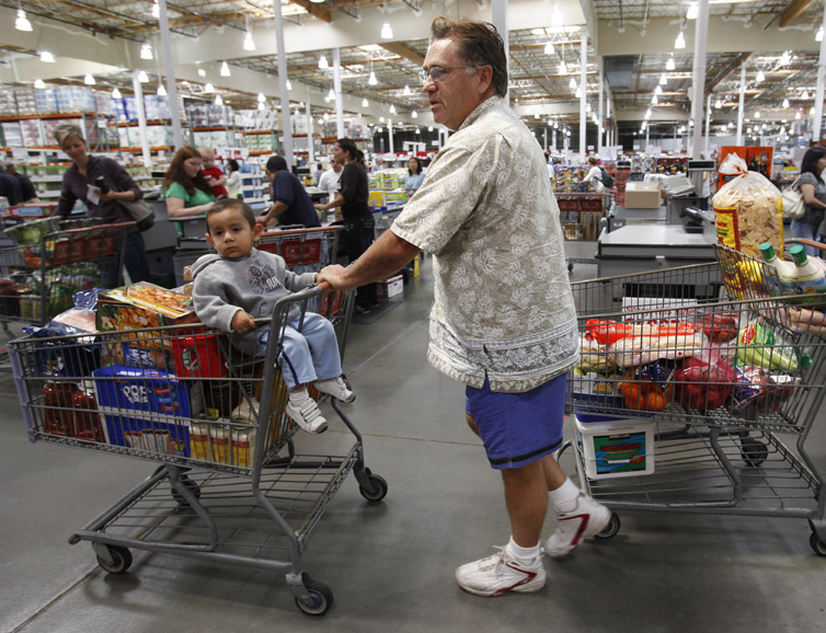 A customer leaves the checkout stand with two carts at Costco in Mountain View, Calif., recently. Americans' view of the economy turned grimmer in September amid escalating job worries, falling to the lowest point since February.