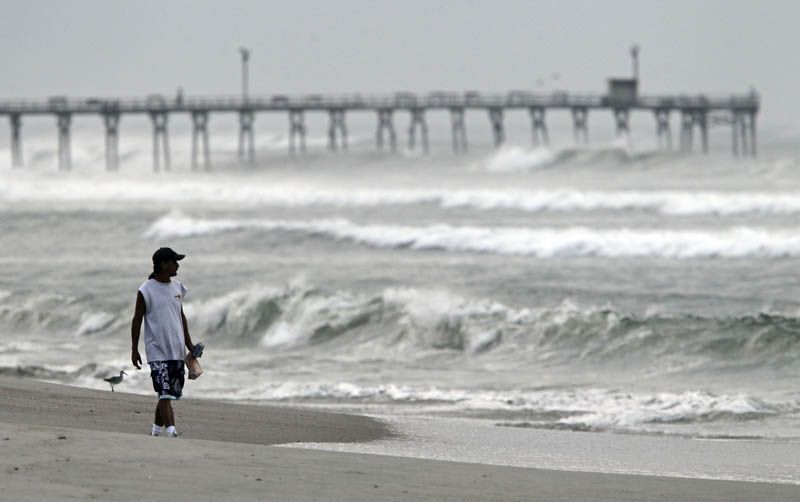 Almon Telling looks at the surf as he walks along the beach in Atlantic Beach, N.C., today.