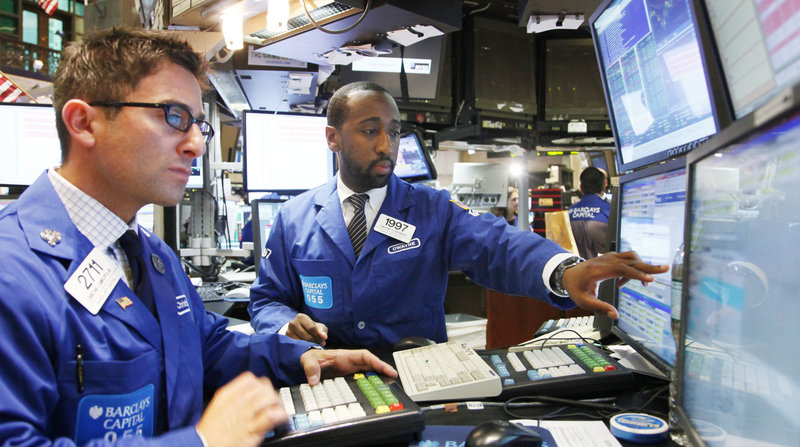 Christian Sanfilippo, Jr., left, and Dwayne Branker, with Barclays Capital, monitor the stock price at the New York Stock Exchange in New York. Stocks are forecast to continue sliding today as investors prepare for more disappointing news.