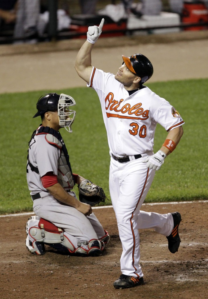 Pointing skyward, Baltimore's Luke Scott crosses home plate in front of Boston catcher Victor Martinez. Scott was 2 for 3 and scored twice.