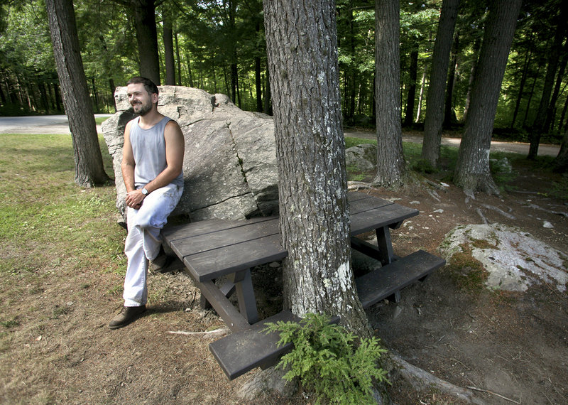 Wade Kavanaugh is working on a series of picnic tables that interact with the natural terrain at Peaks-Kenny State Park. He poses with a completed table near the entrance to the park.