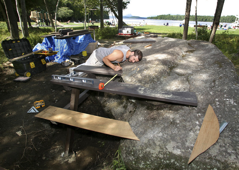 Wade Kavanaugh checks the fit of a table that will use as part of its base one of the huge glacial boulders that dot the park.