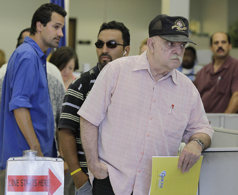 Job seekers wait in line for information on unemployment insurance and work listings in Las Vegas.