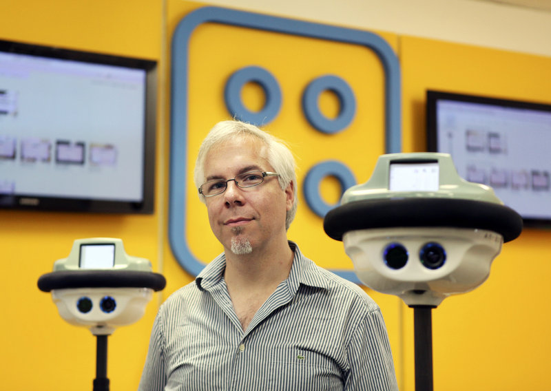 Anybots founder and CEO Trevor Blackwell, with two QB Anybots, says the $15,000 robots can inspect warehouses or factories remotely or provide tech support.