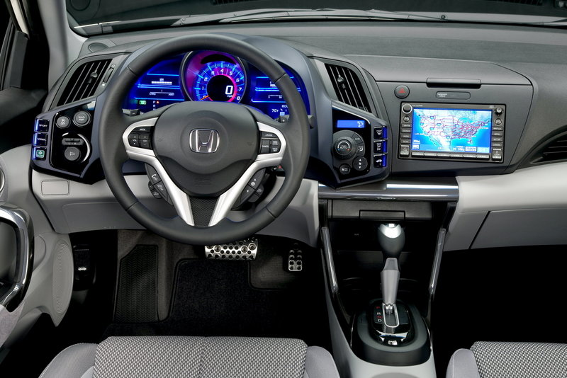 The instrument panel features bright lighting accents and a large, 3D-looking digital speedometer.