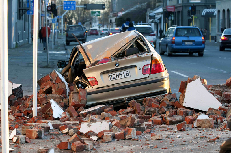 A car crushed by bricks from a building is seen after an earthquake in Christchurch, New Zealand, early today. The mayor declared a state of emergency, warning people that continuing aftershocks could cause masonry to fall from damaged buildings. Looters broke into some shops.