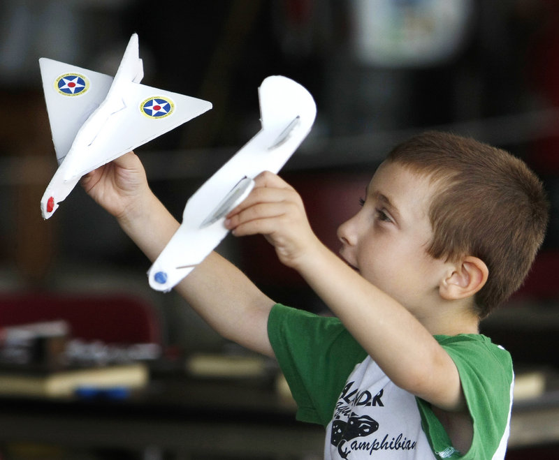 Five-year-old David Howard of Greenland, N.H., has some fun with model airplanes he made at the Vintage Motorcycle Meet and Antique Aeroplane Show. David and his family are spending the weekend in Camden for the Windjammer Festival.