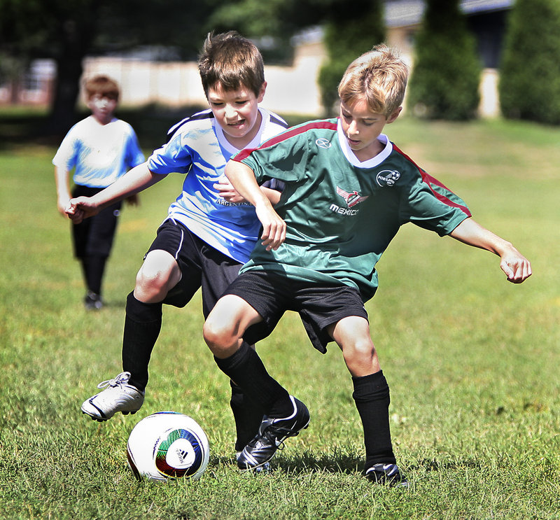 U10 players Gavin Chambers, left, and Max Brown of Portland fight for the ball on Monday during opening day of the Portland Area Youth Soccer Association's U8 and U10 recreational divisions.