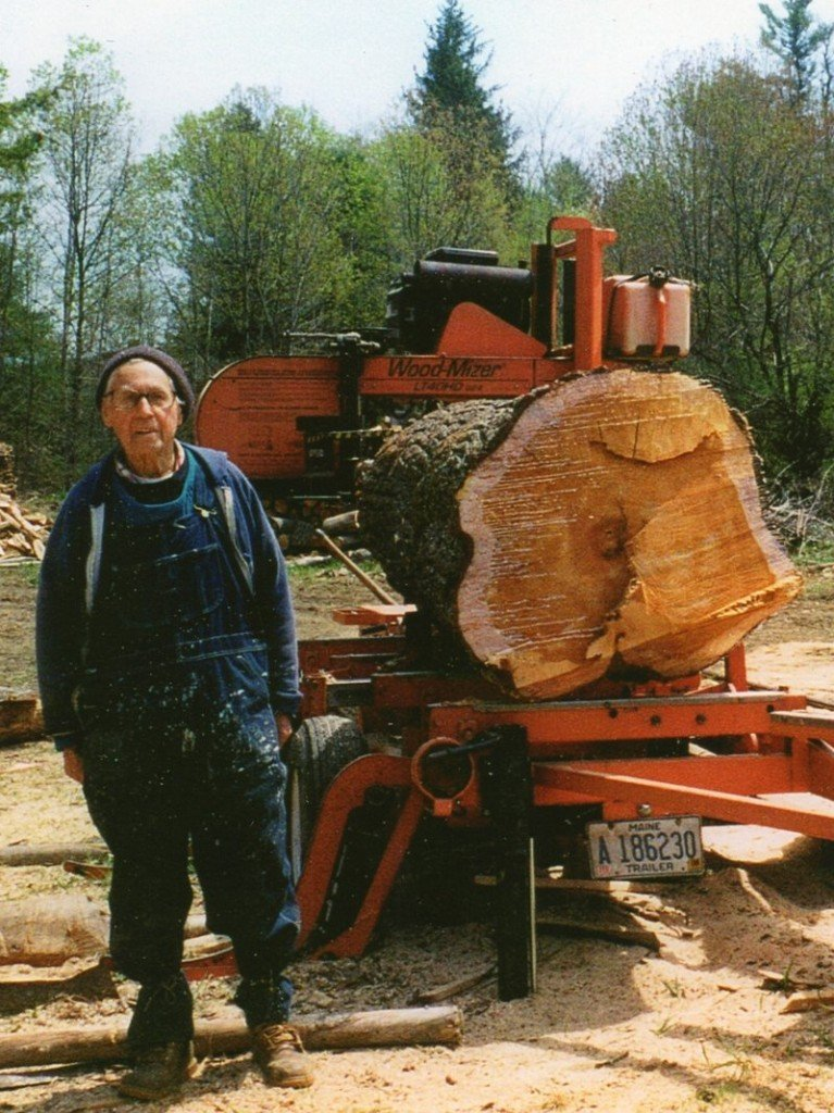 """Emil Dunnell poses on his wood lot with a log ready to be sawed into lumber. """"He got out of the land as much as he possibly could,"""" said a grandson, Brian Dunnell."""