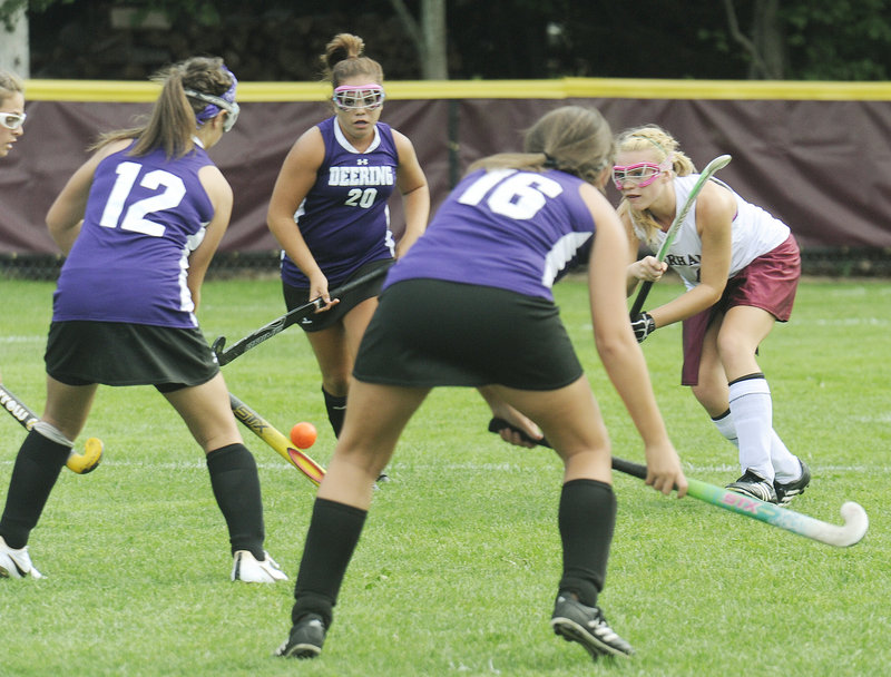 Kelsey Pequinot of Gorham, right, fires a shot through the Deering defense that included Jesse Cinque, 12, and Harmony Therrien, 16, during Gorham's 3-0 victory in an SMAA field hockey game Wednesday at Gorham.