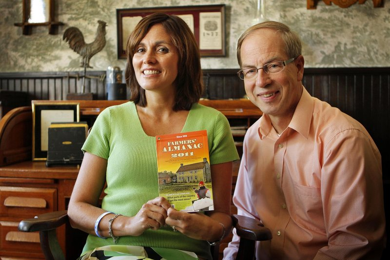 """Farmers' Almanac managing editor Sandi Duncan, left, and editor Peter Geiger pose in Lewiston last month with a copy of the 2011 edition. The publication, which uses a """"secret formula"""" to predict the weather, remains popular with readers."""
