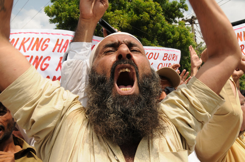 "A protester shouts slogans during a rally Thursday in Multan, Pakistan, in reaction to a Florida pastor's plan to burn copies of the Quran on the ninth anniversary of the Sept. 11 attacks. About 200 people marched in Multan and burned an American flag. President Obama and Defense Secretary Robert Gates asked the Rev. Terry Jones to call off the event, warning it could lead to violence against American forces in Iraq and Afghanistan. ""(It) is completely contrary to our values as Americans,"" Obama said."