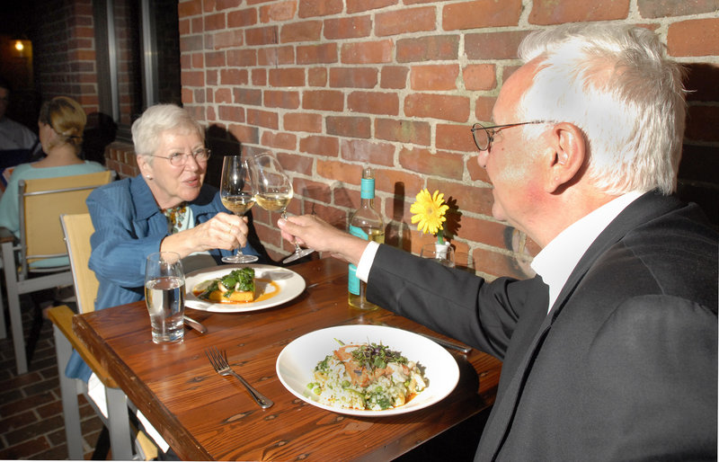 Pat Brown and Jim Morgan raise a toast as they're about to dig into their meals at Havana South in Portland.