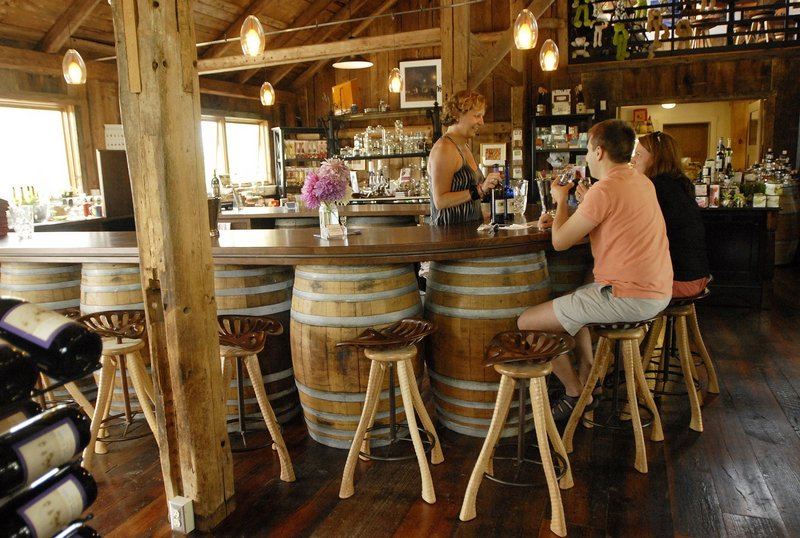 Cellardoor Winery owner Bettina Doulton visits with Kimberly and Aaron Preston of Denver, Colo., in the Lincolnville barn that she renovated to house the business.