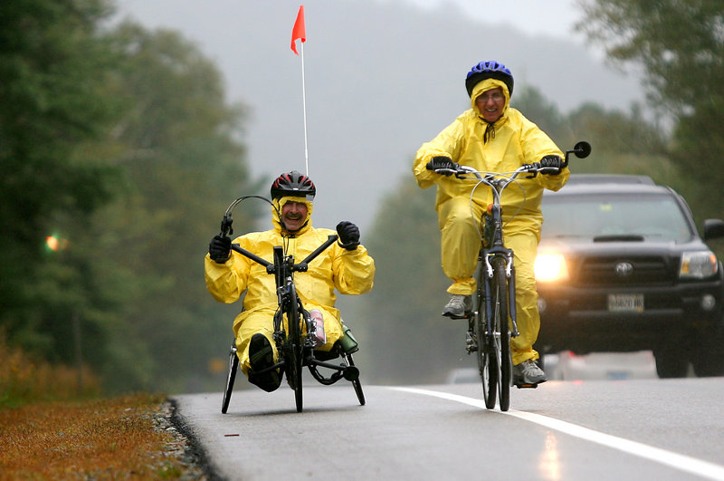 Amputee Joe Severs, left, of Highland, Ill., with wife Mary, bike in the rain on the first day of a three-day bike race Friday in Franconia Notch, N.H. The ride, now in its seventh year, is a fundraiser for Northeast Passage, a UNH program that offers sports and recreation activities for people with disabilities.