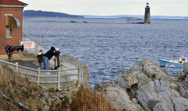David Pape of Indiana, with his children April and Andrew, gets a closer look at Ram Island Ledge Light on a 2008 trip to Maine. The General Services Administration is selling the site.