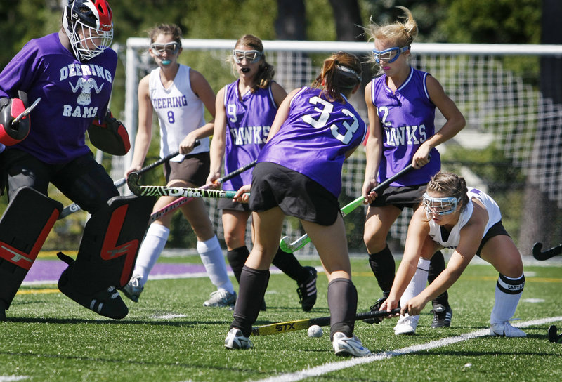 Jesse Cinque, right, of Deering tries to prevent Marshwood's Shea Costin from taking a shot against goalie Caley Presby during their SMAA field hockey game Saturday in Portland. Marshwood won, 2-1.