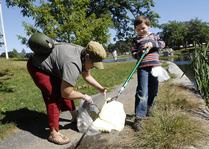 Julin Chapman, 7, helps his mother, Kathryn Irons, of Portland pick up debris at Deering Oaks in Portland Saturday, as part of the 9/11 National Day of Service.