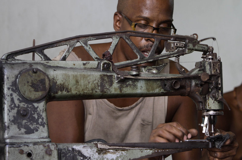 Manuel Cardenas repairs shoes in the state-run La Habanera workshop in Havana on Monday. Raul Castro's government said Monday it will lay off 500,000 state employees by mid-2011 and increase private-sector opportunities – a significant change for the communist-run island.