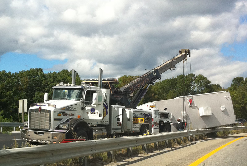 A large camper was damaged as it rolled over and onto a median guardrail Wednesday when the driver of the pickup truck that was hauling it swerved to avoid a post on Interstate 295.