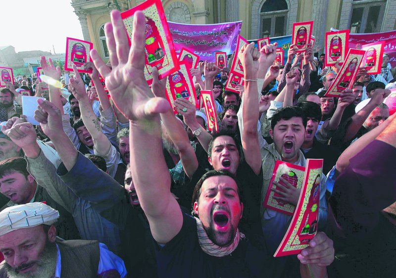 Holding chapters from the Quran, Afghans shout anti-U.S. slogans at a protest after morning prayers outside a mosque in Kabul Wednesday. Police were pelted with rocks, and gunfire was exchanged.