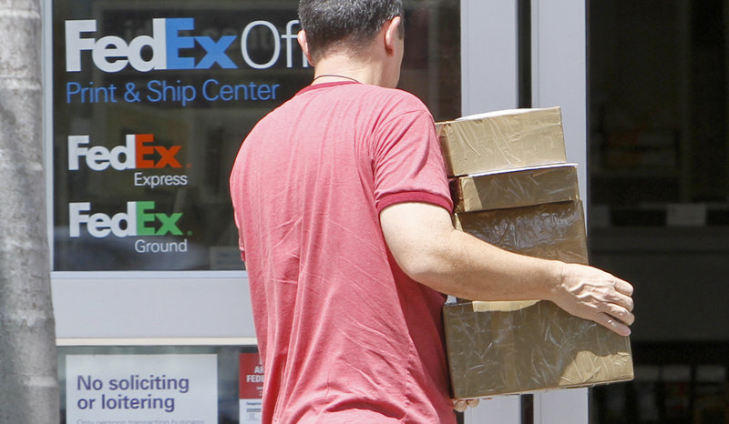 A customer enters a FedEx office in Doral, Fla., loaded with packages. The company, based in Memphis, Tenn., reported Thursday that it earned $1.20 per share in the fiscal first-quarter that ended in August, compared with 58 cents per share a year ago.