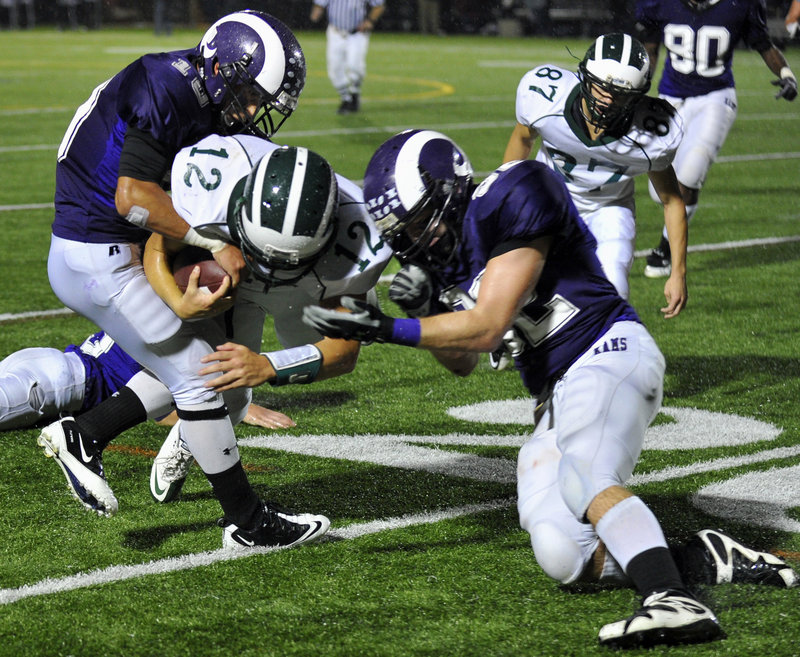 Renaldo Lowry, left, tries to strip the ball away from Bonny Eagle quarterback Matt Rollins as Devon Fitzgerald also closes in during the first half Thursday night.