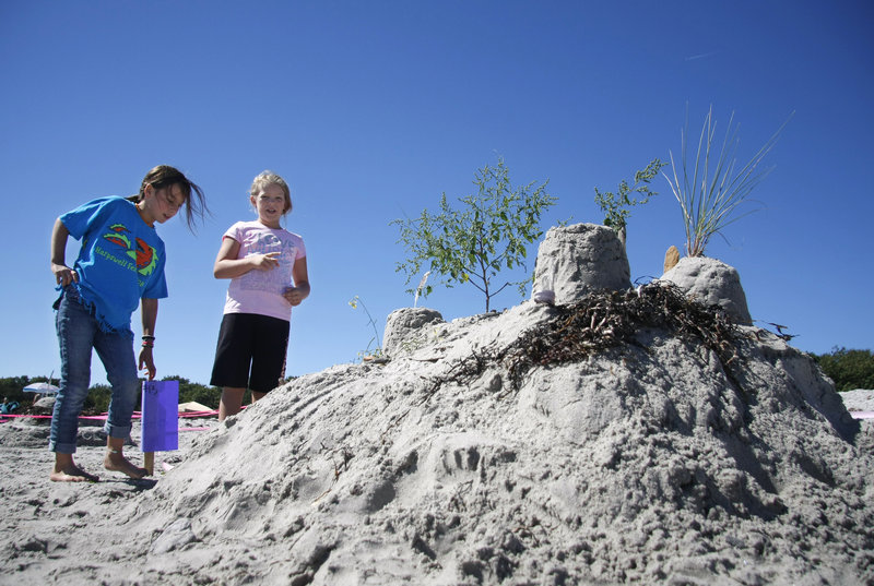 "Ava Clifford, left, and Neeley Hunt, above, both 9 and from Portland, talk about their ""Zen Garden"" sculpture, made with help from Stephanie Hunt and Greg Getchell at Crescent Beach in Cape Elizabeth on Saturday. The girls won an honorable mention."