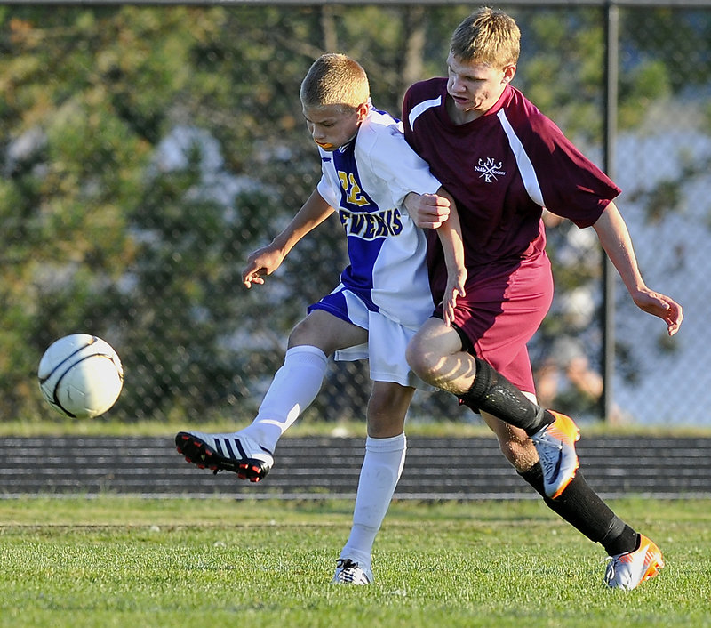 Sterling Weatherbie of Cheverus, left, sends the ball ahead while tangling with Noble's Ben Haskell during an SMAA boys' soccer game Tuesday. Cheverus built a 3-0 lead and held off the Knights for a 4-2 victory at Portland.