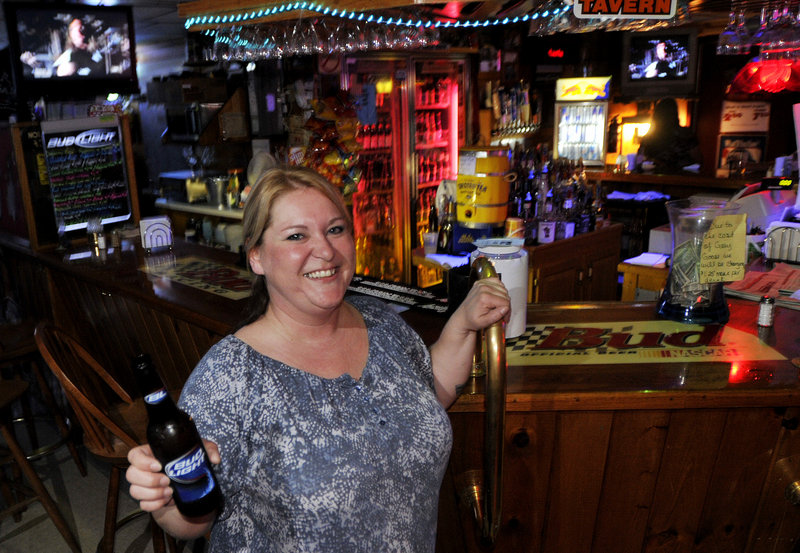 Bartender Krissy Leavitt rounds the corner with a beer for a customer at Buxton Tavern.