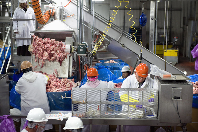 James Achziger, right, samples beef trimmings at the Cargill beef plant in Fort Morgan, Colo. The trimmings are tested for E. coli O157:H7 and turned into ground beef only after testing negative.