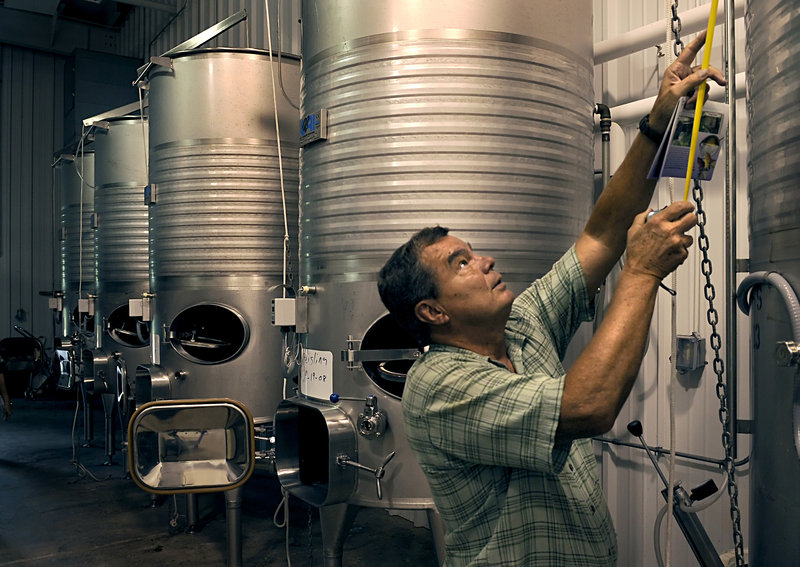 Ken Furr measures a wine vat in the Black Wolf Vineyards winery before the auction of the Dobson, N.C. property, which has been on the market for months with no buyers.