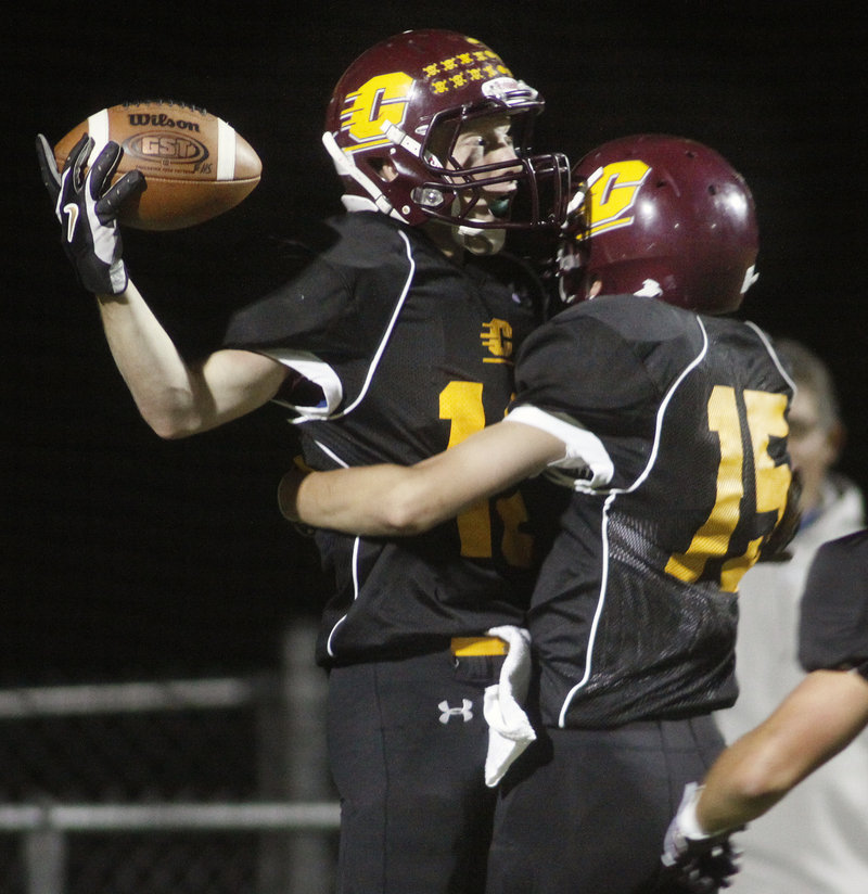 Derek Roberts of Cape Elizabeth, left, is welcomed by Austin Shields after scoring on a 92-yard kickoff return in the first quarter of the 24-21 victory against visiting Falmouth.