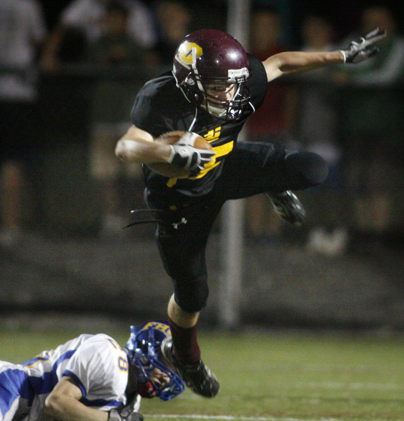 Austin Shields of Cape Elizabeth attempts to keep his balance Friday night while tripped up by Jacob Buhelt of Falmouth in the first quarter. Cape rallied from a 21-7 halftime deficit for a 24-21 victory to stay unbeaten.