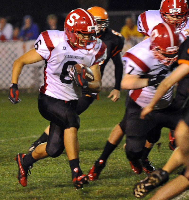 Dennis Liu of Scarborough follows his blockers while picking up yardage in the second half at Waterhouse Field in Biddeford. Scarborough handed the Tigers their first loss.