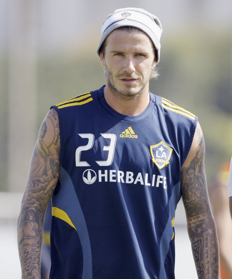 Los Angeles Galaxy's David Beckham watches a soccer training session in Carson, Calif., last week. Beckham's management company says it is taking legal action against a U.S. magazine that published claims the former England captain slept with prostitutes.