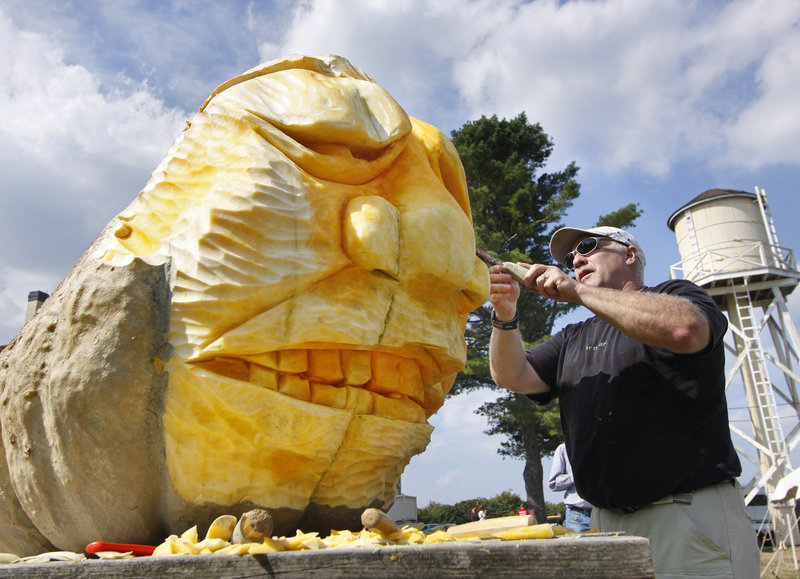 Moe Auger of Alfred makes a sculpture from a giant pumpkin during the Wells Reserve festivities.